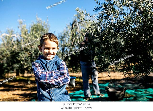 Portrait of smiling boy with his grandfather in olive orchard