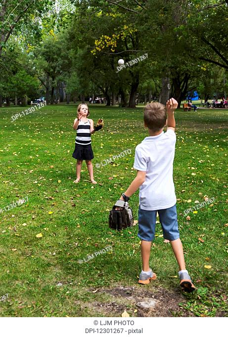 Brother and sister playing catch in a park during a family outing; Edmonton, Alberta, Canada