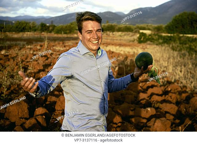 Man with water melon standing on field, in holiday destination Malia, Crete, Greece