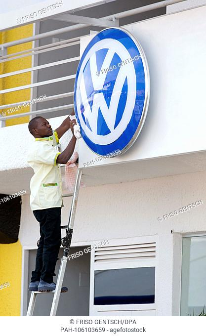 27.06.2018, Rwanda, Kigali: An African Volkswagen employee cleans the logo of the German car manufacturer on the new building of Volkswagen Mobility Solutions...