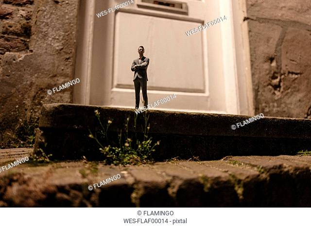 Businessman figurine standing on stairs in front of an entrance door