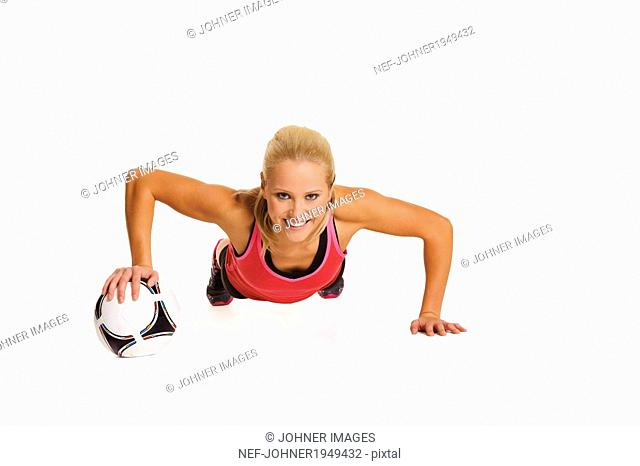 Woman exercising with football, studio shot