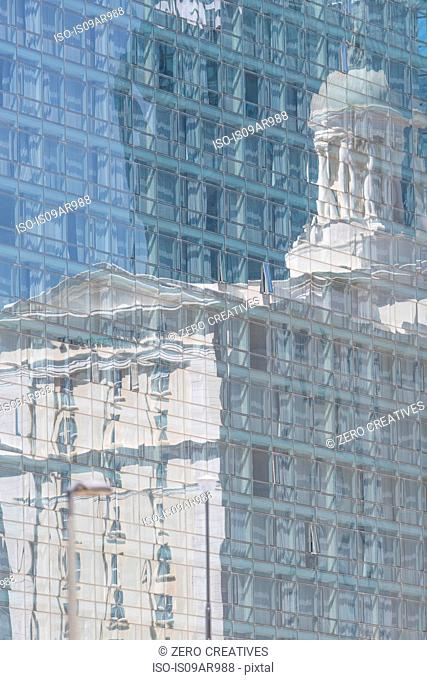 Detail of glass fronted hotel with reflection of historic building