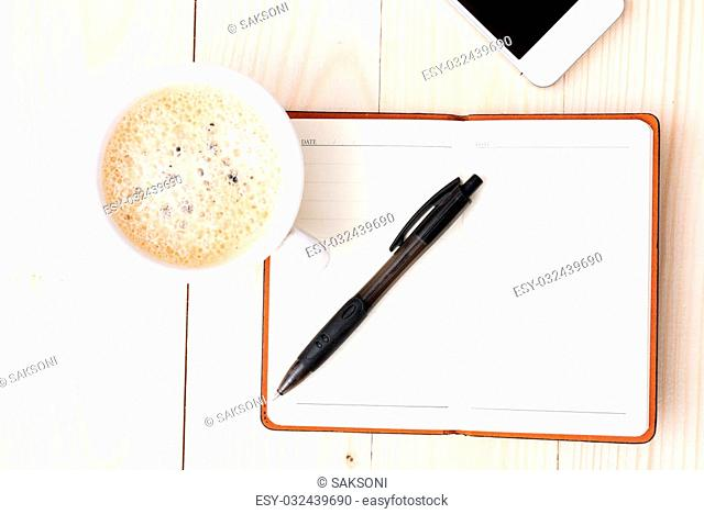 Smartphone with notebook and cup of strong coffee on wooden background