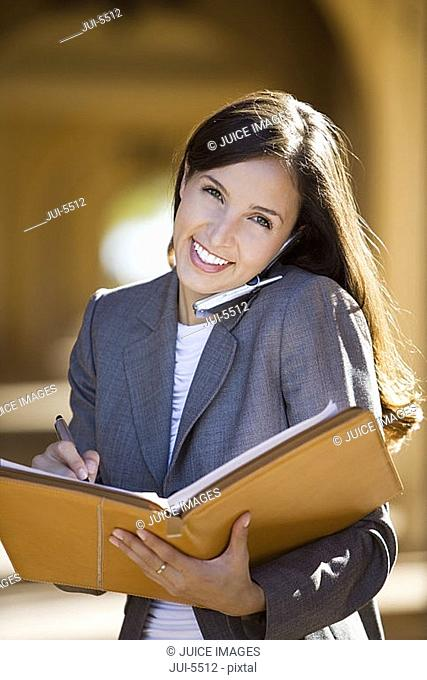 Businesswoman using mobile phone, writing notes in folder, smiling, front view, portrait