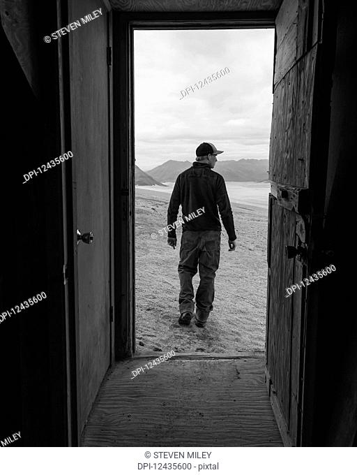 A man and the Valley of Ten Thousand Smokes is framed by the doorway of one of the Baked Mountain Huts in Katmai National Park; Alaska, United States of America
