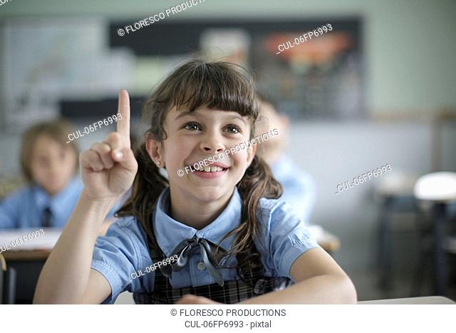 School girl raising hand in class