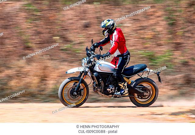 Man speeding on his scrambler type enduro motorbike on dirt track, rear view, Bangkok, Thailand