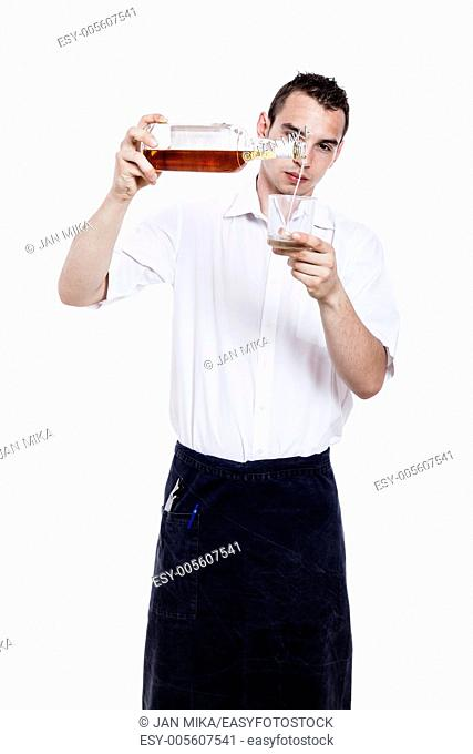 Young waiter pouring glass of whiskey, isolated on white background