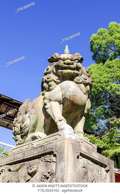 A stone lion-dog guardian, one of a pair guarding the entrance to the Yasaka Shrine, Kyoto, Kansai, Japan