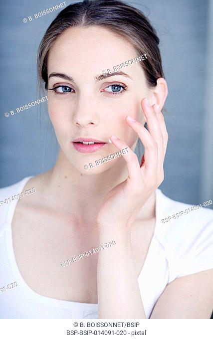 Woman applying cream to treat labial herpes