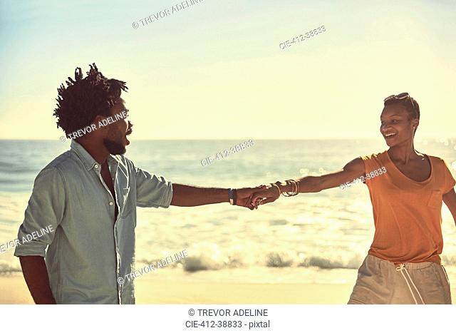 Affectionate young couple holding hands on sunny summer beach