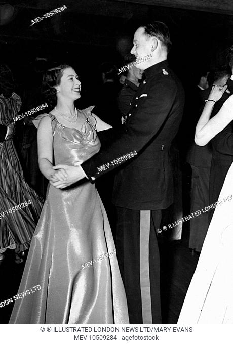 Princess Elizabeth (Queen Elizabeth II) attending a ball held at the Old House Hotel in aid of the NSPCC. She is pictured smiling as she dances with Captain...