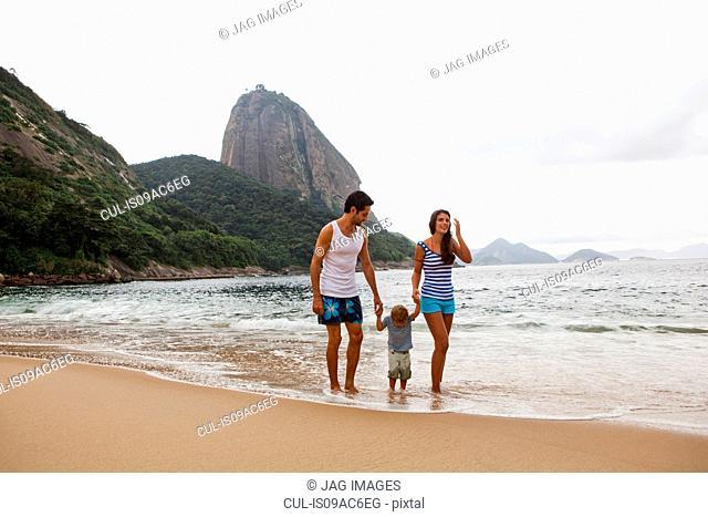 Family walking on beach holding hands, Rio de Janeiro, Brazil