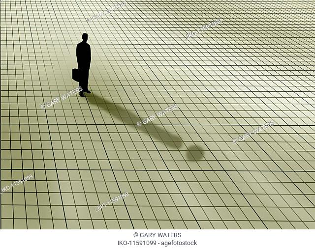 Businessman standing on graph paper grid casting exclamation mark shadow