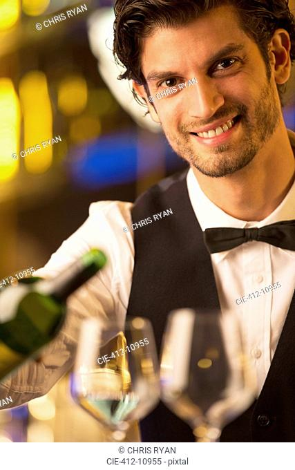 Close up portrait of well dressed bartender pouring wine
