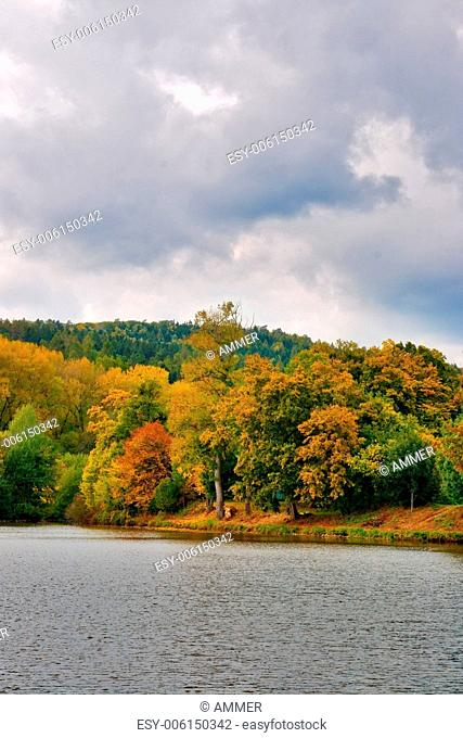 Autumnly colored trees on the shore of pond with cloudy heaven, Southern Moravia, Czech Republic, Central Europe