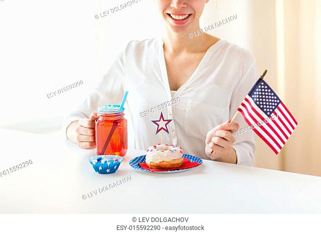 independence day, celebration, patriotism and holidays concept - close up of happy woman with donut celebrating 4th july