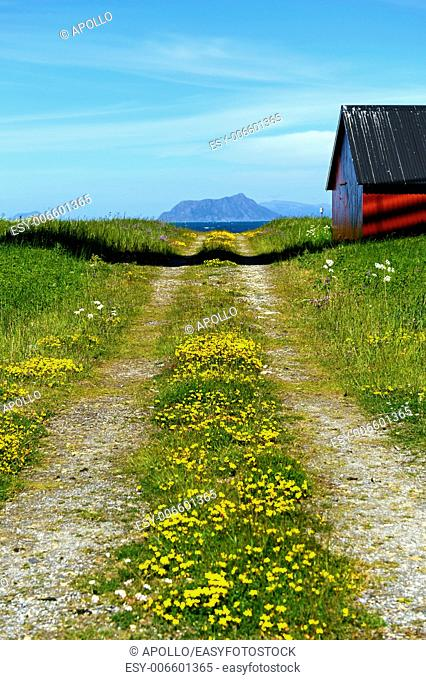 Dirt road with mountain range and barn, Norway