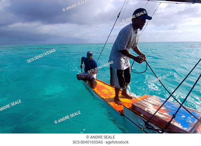 Marshalhese men steering a traditional outrigger canoe, Ailuk atoll, Marshall Islands, Pacific