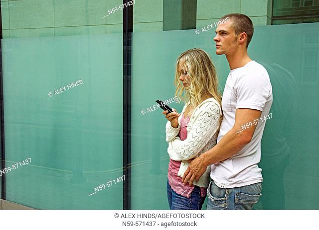 Attractive young urban couple, she is looking at messages on mobile phone