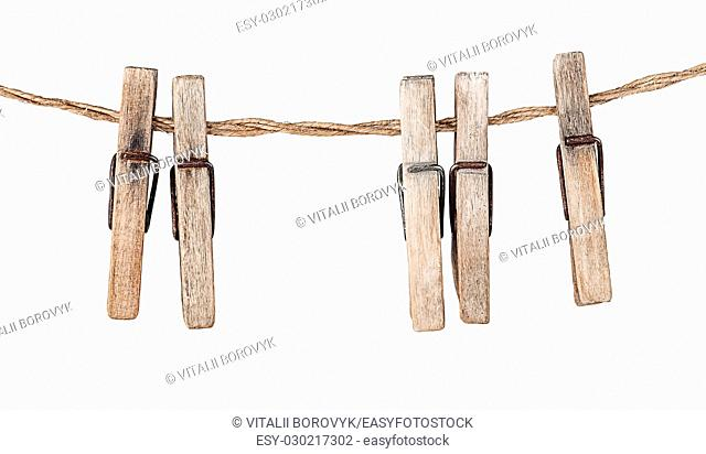 Five old clothespins on rope isolated on white background