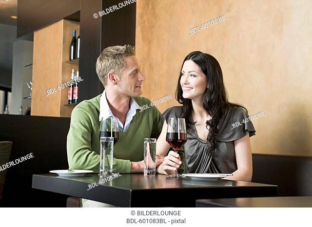 young couple sitting at restaurant with glasses of red wine