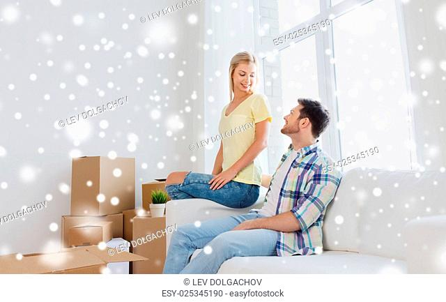 moving, people and real estate concept - happy couple with cardboard boxes on sofa at new home over snow
