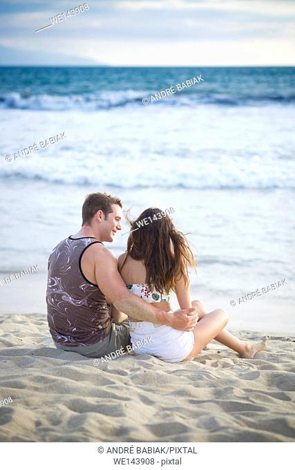 Back side of young couple in their 20s sitting at the beach