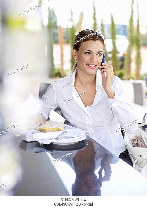 Young woman using mobile phone in outdoor hotel restaurant