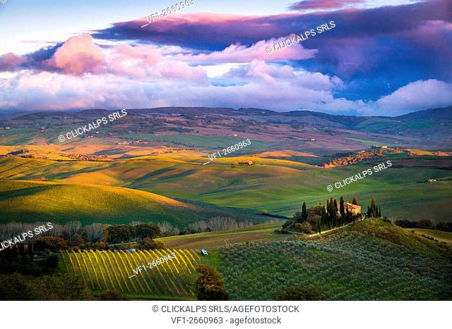 San Quirico d'Orcia, Tuscany, Italy. Sunset over the valley with some farmhouses and a very cloudy sky
