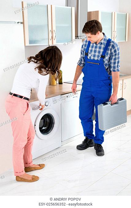 Young Woman Showing Damage In Washing Machine To Repairman In Kitchen Room