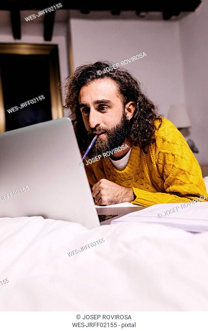 Young man lying in bed at home using laptop