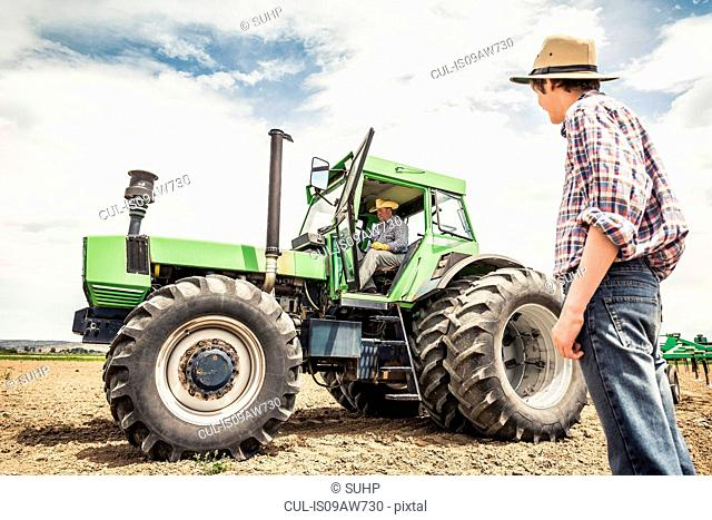 Teenage boy watching farmer driving tractor in ploughed field