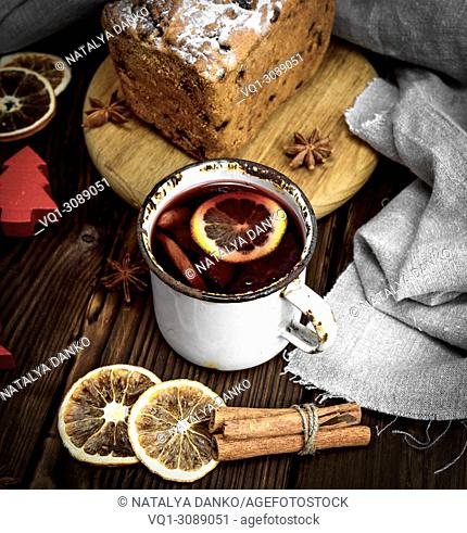 mulled wine in a white iron mug and baked pie with dried fruits, top view