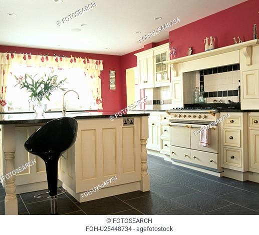 Red country kitchen with fitted cream units