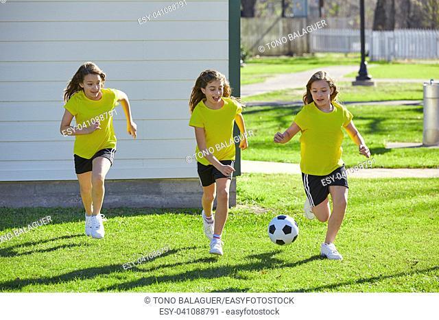 Friend girls teens playing football soccer in a park turf grass