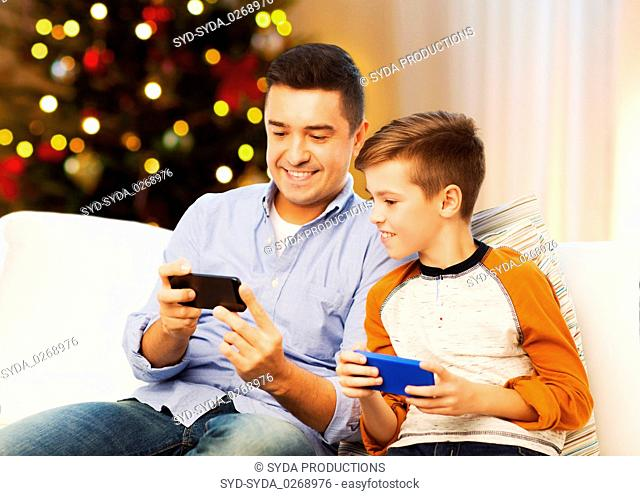 happy father and son with smartphones on christmas