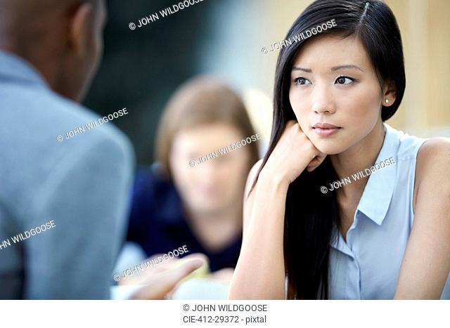 Serious businesswoman listening to businessman