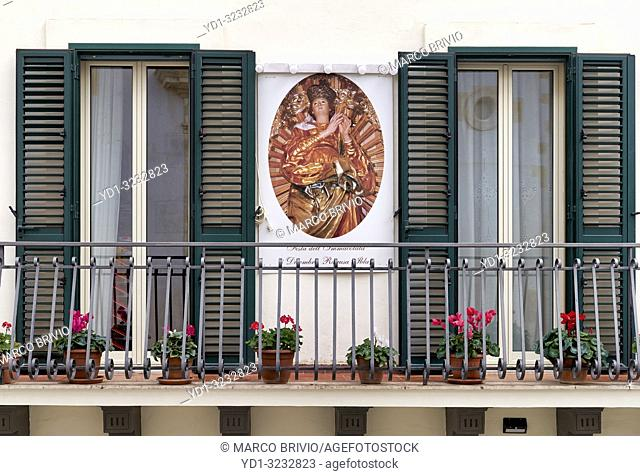 A balcony of a house in Ragusa Ibla Sicily Italy with a sacred religious image on the wall