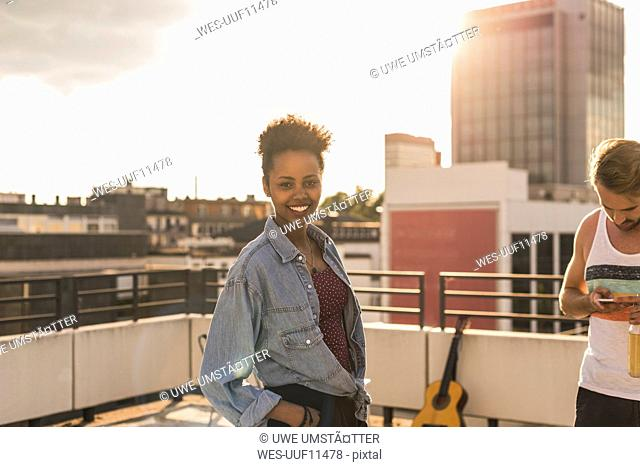 Portrait of smiling young woman on a rooftop party