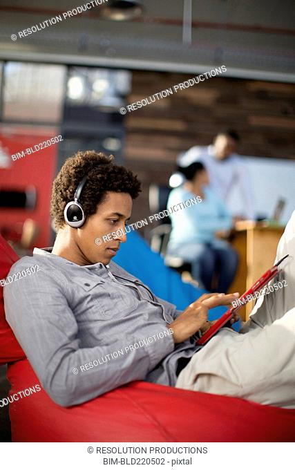Mixed race businessman using digital tablet in office lounge