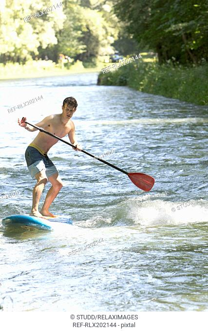 Full length of young man on paddleboard in river