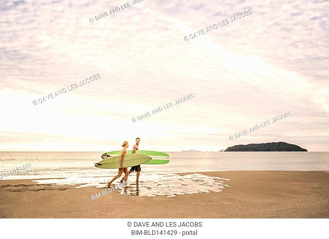 Caucasian couple carrying surfboards on beach