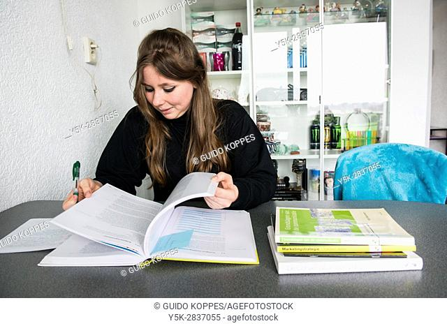 Zwijndrecht, Netherlands. Young adult woman studying at her living room table to obtain her Bachelor's Degree in Marketing and Communication