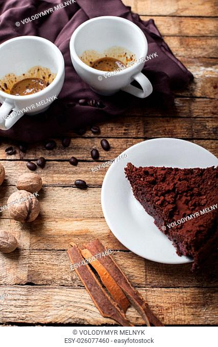 Chocolate cake, two cups of coffee and cinnamon sticks on wooden table with coffee beans and nuts
