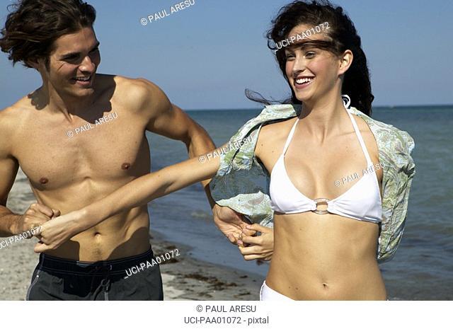 Young Hispanic couple walking on beach