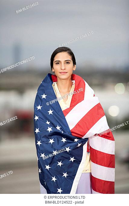 Woman wrapped in American flag outdoors