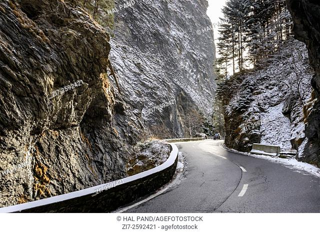 winter landscape with the small curvy road among the steep rocks in ViaMala gorge near Thusis, Graubunden, Switzerland