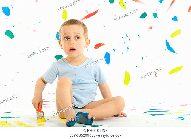 Adorable 3 year old boy child creatively stains on the wall, floor with colourful paint. Mess of paint on wall, floor and everywhere